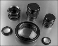 Lens barrels and glass Front row left: rear element of a Kodak 71/2″ projection lens… middle- 5″ diameter magnifier mounted with 95mm adaptor… right- lens element from a defunct videocam. Back row left-large format Artar 'barrel lens' with aperture diaphragm and waterhouse slot with it own native lens elements removed, it has 67mm accessory threads on both ends… middle- medium format 645 150mm leaf shutter lens barrel with aperture diaphragm, with lens elements removed… right-medium format 645 80mm w/aperture diaphragm, with its lens elements removed.   I use the rear element of the Kodak projection lens, and the lens element from my dead v/cam on the MF 645 80mm barrel, and the 5″ magnifier on both the LF Artar barrel/shell and the MF 645 150mm leaf shutter barrel/shell.