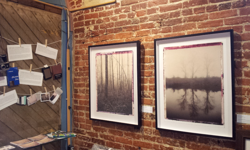Photograph showing two of Bill Wolff's framed prints and some of his information about Polaroid cameras and film.