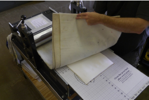 Pull the wool blankets over the paper and plates. Run everything through the press to make a print.